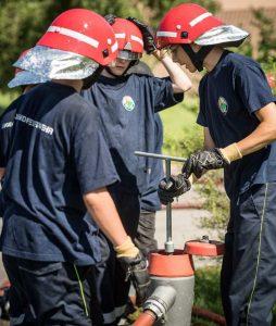Drei angehörige der Jugendfeuerwehr beim Öffnen eines Hydranten